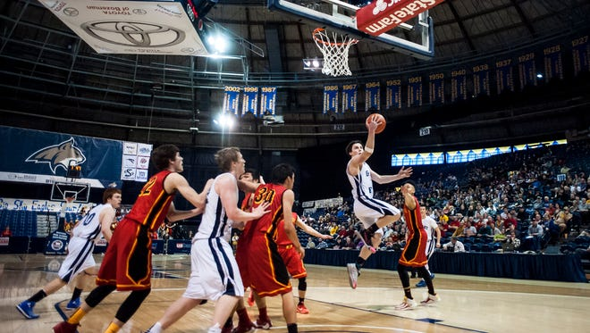 Great Falls' Daniel Silverstein leaps past Missoula Hellgate players to shoot during the State AA Tournament in MSU's Brick Breeden Fieldhouse Thursday.