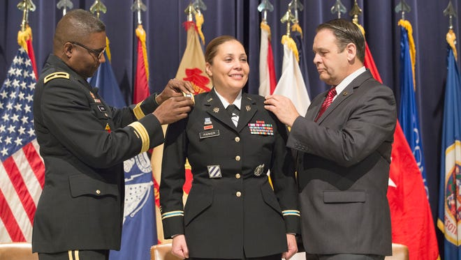 From left, Picatinny Arsenal senior commander Brig. Gen. Patrick W. Burden changes the rank on the shoulders of Col. Ingrid A. Parker from lieutenant colonel to colonel with Davis Tindoll, Jr. Atlantic Region Director, Installation Management Command. Parker, Garrison Commander of Picatinny Arsenal, was officially promoted to colonel in the U.S. Army by Brig. Gen. Patrick W. Burden, Senior Commander during a ceremony at the post. Parker has been assigned as the Garrison Commander to Picatinny Arsenal since 2014. She is responsible for the welfare, maintenance and security of Picatinny Arsenal, which has 6,500 acres, 84 miles of roads, more than 900 structures and more than 6,000 employees. Friday, March 11, 2016. Rockaway Township, NJ.Special to NJ Press Media/Karen Mancinelli/Daily RecordMOR 0312 Picatinny Promotion