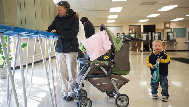 Sara Cieslak of Plover, left, votes in the spring election while her son Noah, 2, holds her bag at the Plover Municipal Center, Tuesday, April 5, 2016.