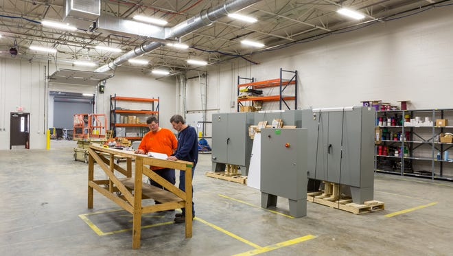 Justin Anderson, panel shop fabricator, and Chuck Little, panel shop manager of Gettle Incorporated, review job plans in the expanded panel assembly shop of the company's new office at 325 Busser Road in Emigsville.