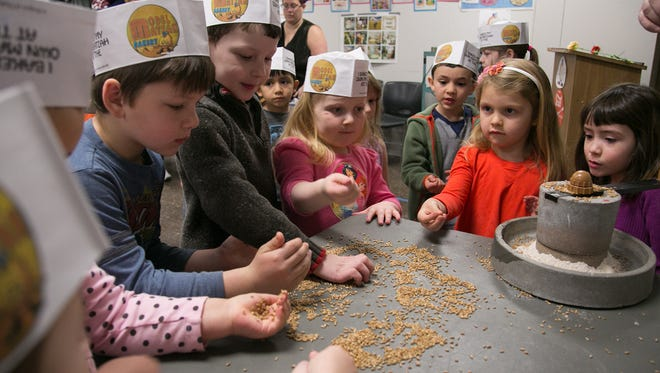 Children check out grain as they learn to make matzo at the Jewish Community Center in Rochester on April 10.
