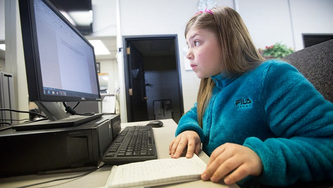 Chloe Vine, 9, works on a story about her dad, Going Out reporter Nathan Vine, at the Stevens Point Journal Media office, Thursday, April 28, 2016.