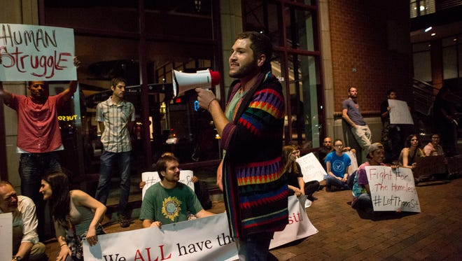 Wes Wisner (center) speaks while he and others protest the Tempe ordinance that does not allow sitting or laying on a down town sidewalk.