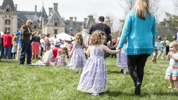 Children and their families enjoy the sun on the front lawn following the annual Biltmore Estate Easter egg hunt. The Biltmore Estate will offer free entry for moms on Mother's Day with the purchase of a youth or adult ticket.