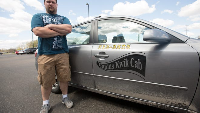 Rapids Kwik Cab owner Chris Wickersham stands next to one of his vehicles in Wisconsin Rapids, Monday, May 2, 2016.