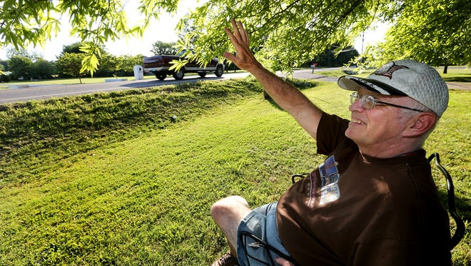 Paul Tidwell sits on his front lawn and waves at passers by along Old Nashville Highway on Thursday, May 19, 2016. Occationally along with waves he also instigates car horns blowing and voices screaming and trailing out Hey Paul.