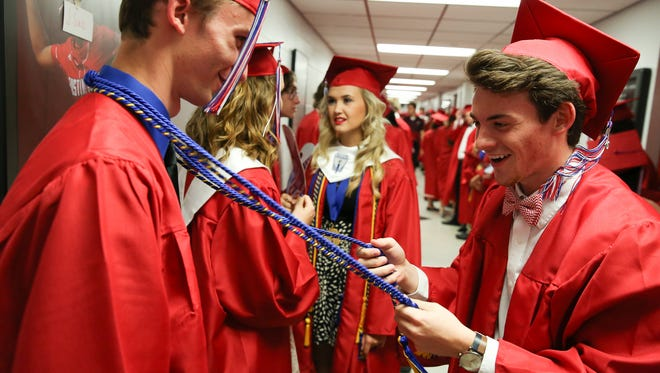 Graduating senior Daniel Strong, right, helps a classmate with his honor cords before the Montgomery Central High School commencement ceremony at Austin Peay State University's Dunn Center on Friday, May 27, 2016, in Clarksville, Tenn.