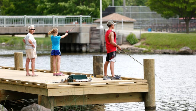Bonnie Krupp watches her grandchildren Jenna and Dakota fish off a new pier on Oven Island Thursday.