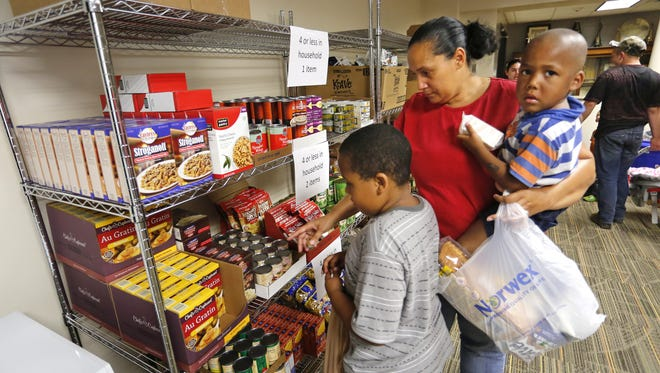 With three-year-old son Micheal Meyer in her arms, Joline Meyer points out to her son Jaikeam Jones food items to bag at the food pantry September 10, inside Oakland Elementary School. Oakland Elementary together with Food Finders Food Bank and Congress Street United Methodist Church opened the food pantry to help feed students and their families who are struggling with food insecurity.