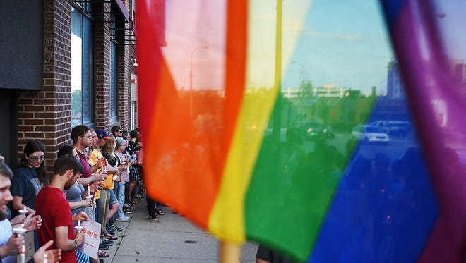 Dozens of vigil participants stand outside Club David at the corner of 10th Street and Dakota Avenue during a vigil in downtown Sioux Falls Monday, June 13, 2016, in response to the mass shooting at the Pulse nightclub in Orlando, Fla. The vigil was put on by the South Dakota Peace and Justice Center and the Center for Equality.