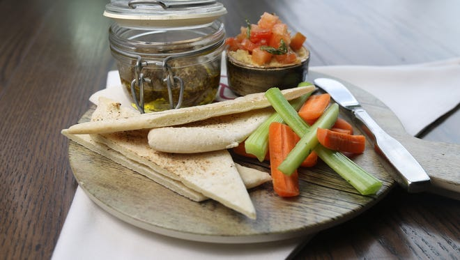 Hummus and yogurt cheese is thick Greek yogurt rolled in a spice blend, classic chickpea hummus and veggie sticks served with flatbread at PJ's - SentryWorld in Stevens Point, Thursday, June 9, 2016.