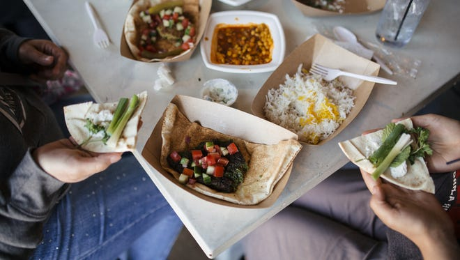 """Diners eat Iranian sabzi khordan -- fresh herbs, radish and cheese in a pita -- at Peace Meal Kitchen's """"Taste of Iran"""" pop-up at Our/Detroit in Southwest Detroit April 24, 2016. Also pictured are kookoo sabzi, kotlet sandwich and khoresh gheymeh bademjan."""