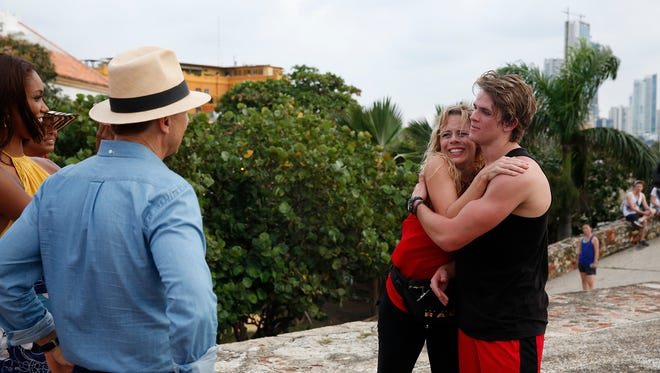 """Bros Being Jocks""--Host Phil Keoghan (left) greets Mother/Son team Sheri (center) and Cole (right) at the Pit Stop at Baluarte de Santiago on Cartagena's old city wall on THE AMAZING RACE, Friday, Feb. 26 (8:00-9:00 PM, ET/PT) on the CBS Television Network. Photo: Robert Voets/CBS ©2016 CBS Broadcasting, Inc. All Rights Reserved"