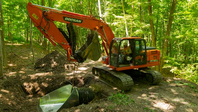 Steve Hill of Wysox Pennsylvania, working for M.R. Dirt of Towanda Pennsylvania operates an excavator as he installed a drainage pipe for the Black Diamond Trail north of the Perry City Road in the Town of Ulysses on June 20.
