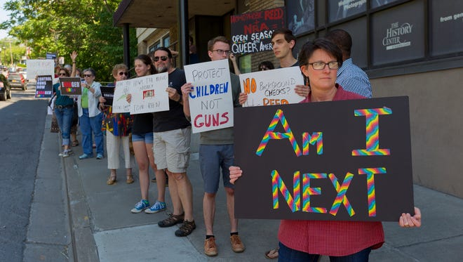 Deborah Cipolla-Dennis, of Dryden, foreground, and about 25 others protest Rep. Tom Reed's stance on guns Friday afternoon in front of his Ithaca office on East State Street.