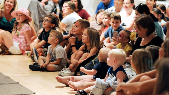 Local families watch a performance at Family Fun Day 2015.