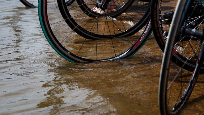 Members of the RAGBRAI preride team dip their tire in the Mississippi after finishing the route during preride on Saturday, June 11, 2016.