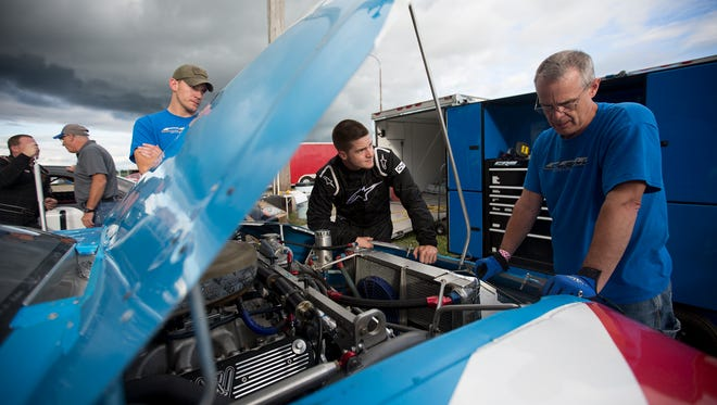 Colin Reffner, center, Grant Goldberg, left, and his uncle Bryan Reffner, right, look over Reffner's car in between races at Golden Sands Speedway in Wisconsin Rapids, Friday, July 8, 2016.