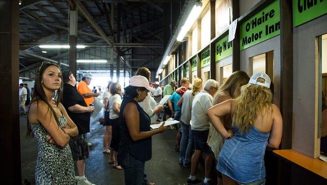 Gambling hopefuls stand in line at the gambling window below the Grandstands during the second day of the Great Falls Horse Race Meet on Sunday. The handle for the first two days of racing totals around $200,000.