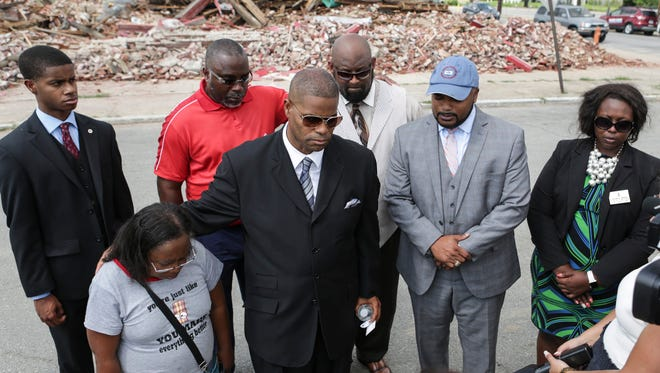 Jacqueline Whitaker, front left, the spouse of the man killed in the building that collapsed Friday at 28th Street and Grand Avenue, prays with others at the former building's site. July 26, 2016