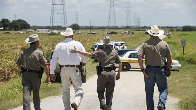 """Texas DPS Trooper Robbie Barrera, center right, puts her arm around Caldwell County Sheriff Daniel Law as he arrives on the scene of a hot air balloon crash Saturday, July 30, 2016 near Lockhart, Texas, causing what authorities described as a """"significant loss of life.""""  (Ralph Barrera/Austin American-Statesman via AP)"""