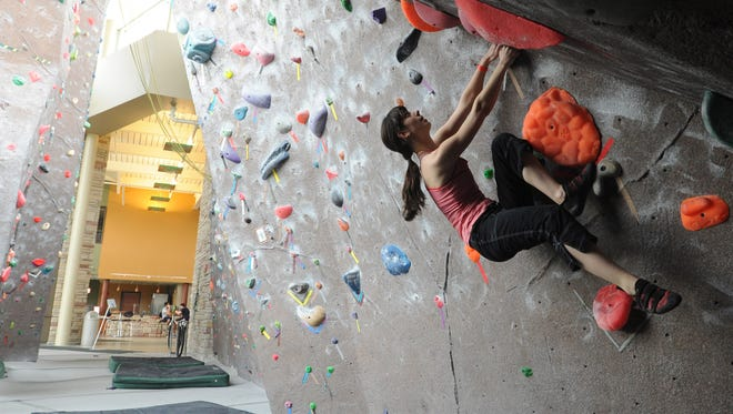Kat Russo, a senior fine arts major, manuvers the climbing wall at the CSU Recreation Center Friday April 5, 2013.