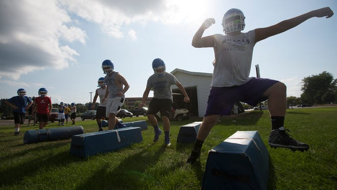 Assumption football players go through footwork drills on the first day of football practice at Assumption High School, Tuesday, Aug. 2, 2016.