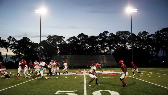 Immoral football players run plays during football practice at Immokalee High School on Thursday, August 11, 2016.