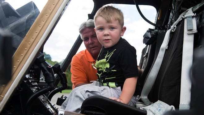 """In this Aug. 10, 2016, photo, Knox County Sheriff Jimmy """"J.J."""" Jones gives 3-year-old Joshua Collins a tour of a law enforcement helicopter in Knoxville. The youngster from Rocky Top, Tenn., is a big fan of Batman and thinks every law enforcement officer is the super hero, so his mother has taken him to visit several police departments. But Wednesday's stop was special because he was getting to see a """"bat copter."""""""