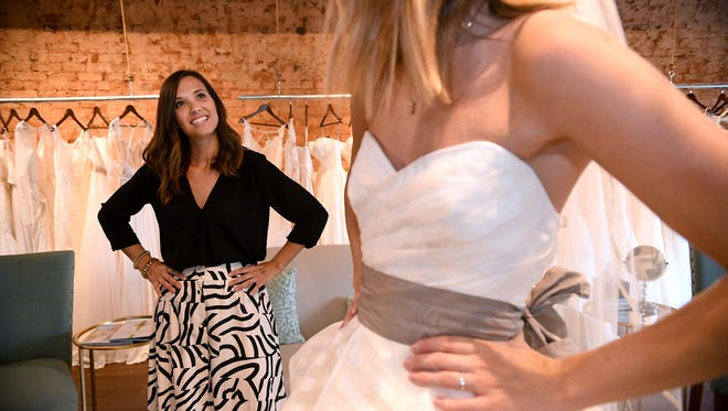 Johna Lutz, bridal stylist and store manager at The White Magnolia, helps Toni Rabine try on a wedding dress on Thursday.