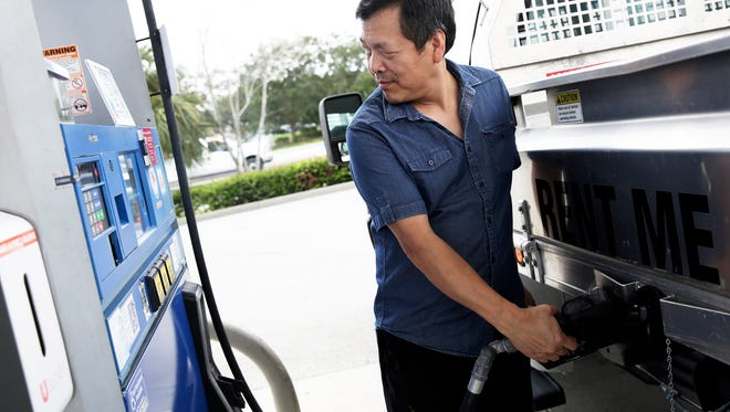 Mark Cheng of Naples pumps gas at the Mobil station on the corner of Airport-Pulling and Pine Ridge roads in North Naples on Monday, Aug. 22, 2016.