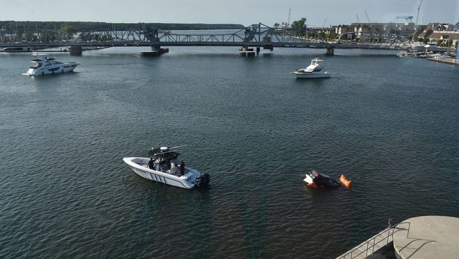 The Door County Sheriff's Department boat tows a Buick Lucerne across the Sturgeon Bay Shipping Channel to Sawyer Park boat Thursday, Aug. 25, 2016. The car rolled into the water at CenterPointe Yacht Services at right. A passenger managed to escape.