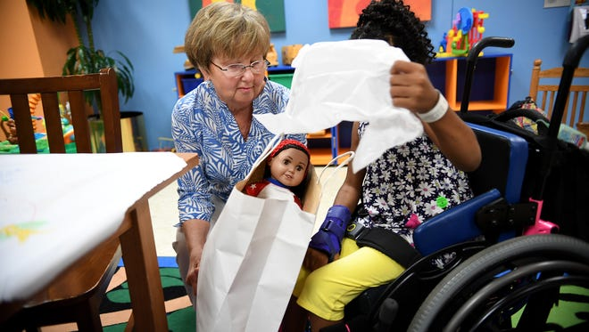 Pat Blackburn, who makes doll clothing and donates the dolls and clothing to Shriners Hospital for Children's patients, gives CatLynn Poe, 8, one of the dolls in person on Tuesday.