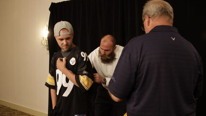 Ryan Puetz from Dover has former Pittsburgh Steelers player Brett Keisel sign his jersey before the Fourth Annual Children´s Benefit Dinner hosted by the York County Development Center at the Wyndham Garden York in West Manchester Township on Thursday.