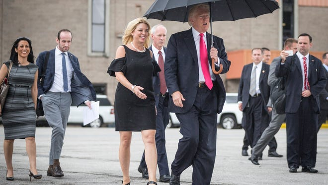 Republican presidential candidate Donald Trump walks in the rain with Florida Attorney General Pam Bondi last month in Tampa, Fla.