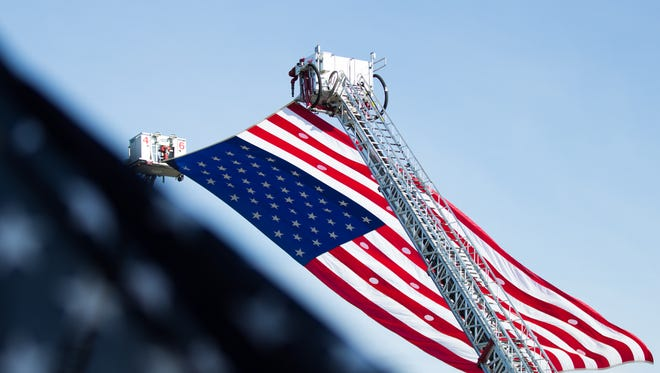 An American flag is suspended between two firetruck ladders over the 9/11 Healing Field at West Manheim Elementary School in Hanover.