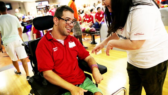 Volunteer Daniela Franco helps athlete Paul Stevens on his turn to bowl during Collier County Special Olympics bowling at Bowland Woodside in Naples on Saturday, Sept. 17, 2016.