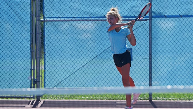 Lincoln's Meredith Benson returns the ball to St. Thomas More's Grace Wittenberg and Megan Fenske during a doubles match Monday, Sept. 19, 2016, at Lincoln High School in Sioux Falls.