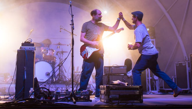 Dogfish Head founder Sam Calagione high-fives Built To Spill's Doug Martsch at Analog-A-Go-Go at Bellevue State Park last year.