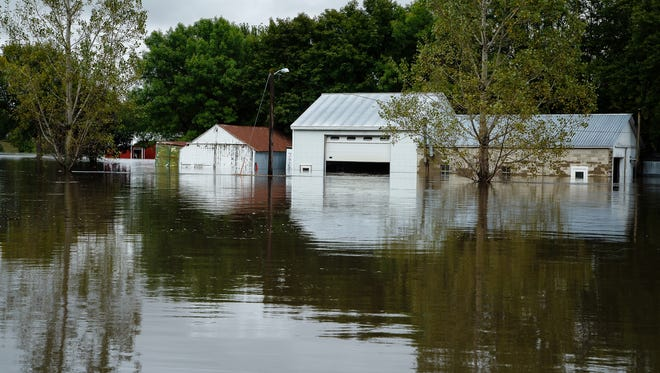 Homes and businesses remain flooded on Thursday, Sept. 22, 2016, in Greene.