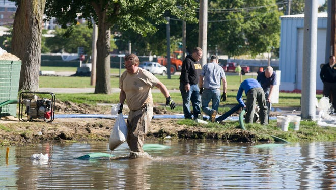 Sgt. James Gales works to keep floodwaters at bay near the Linn County Sheriff's Office in Cedar Rapids, Iowa, Tuesday, Sept. 27, 2016.