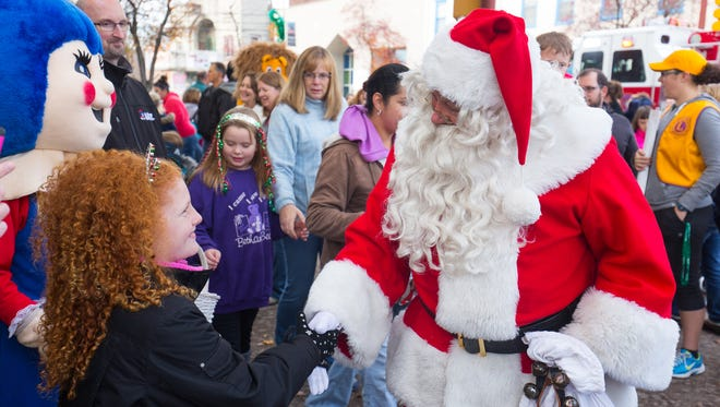 Santa Claus shakes the hand of a young girl during the Hanover Christmas Parade on Nov. 27.