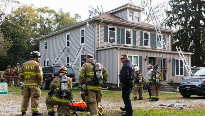 Emergency crews work at the scene of a house fire on the 100 block of Municipal Road in Berwick Township on Monday. The fire started on the back porch, spread into the house and caused extensive damage throughout the building.