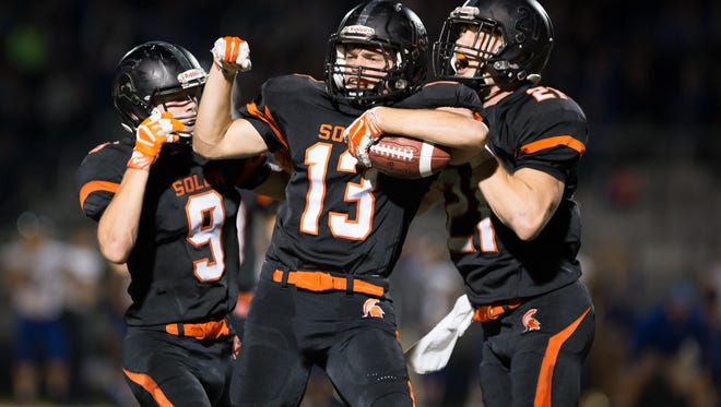 Solon's Grant Goldsberry (9), Austin Kennedy (13), and Bo Black (21) celebrate an interception by Kennedy in the second quarter at Solon High School on Friday, October 28, 2016.