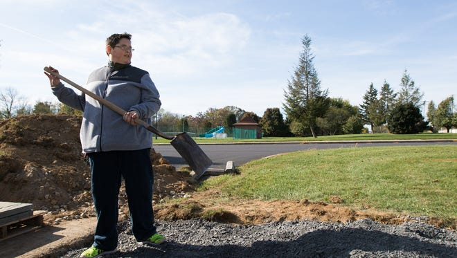 Boy Scout Travis Hartlaub uses a shovel to level out a mound of gravel in Littlestown Community Park on October 29, 2016. Several volunteers gathered in the park on Saturday to help Hartlaub construct a Veterans Memorial for his Eagle Scout Service Project.