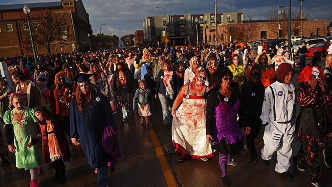 A horde of Sioux Falls Zombie Walk participants make their way through downtown Sioux Falls during the Zombie Walk Saturday, Oct. 29, 2016.