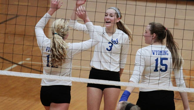 With jubilation on their faces, Reagan Raymer (L), Mia Kraft (3) and Claire Carmichael (15), come together to high-five after a Wyoming Cowboy point.  Wyoming went down to Logan Elm in the Region 8 semifinals at Butler High School Wednesday, November 2, 2016.