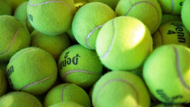 FILE - Practice tennis balls are in a bucket at Plaza Racquet Club in Palm Springs, Calif. on March 5, 2015.
