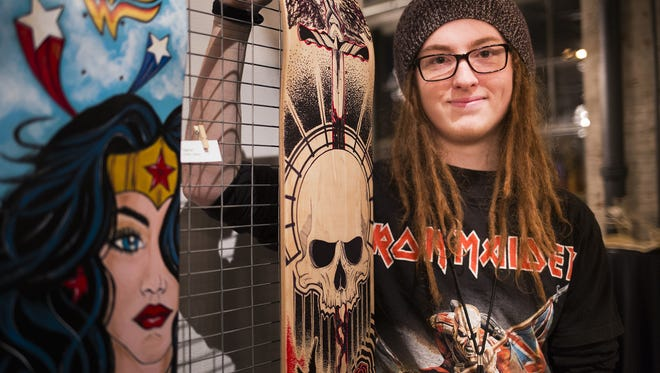 Artist Oliver D. Scott, 17, of West York, poses with his board, Trash Polka Skull, center. Art enthusiasts attend Decked Out, an art show and auction featuring artist-decorated wooden skateboard decks, at The Bond in York, Saturday, November 12, 2016.