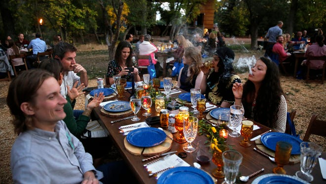 In this Oct. 2, 2016, photo, diners smoke marijuana as they eat dishes prepared by chefs during an evening of pairings of fine food and craft marijuana strains served to invited guests dining at Planet Bluegrass, an outdoor venue in Lyons, Colo. Denver has approved a first-in-the-nation law allowing people to use marijuana in bars and restaurants.